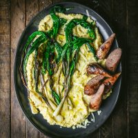 Creamy Cheddar Polenta with Sausage and Charred Ramps